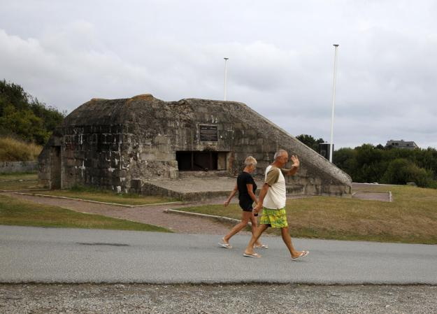 Tourists walk past a former German bunker overlooking the D-Day landing zone on Omaha Beach near Saint Laurent sur Mer, France, August 24, 2013. (REUTERS/Chris Helgren)