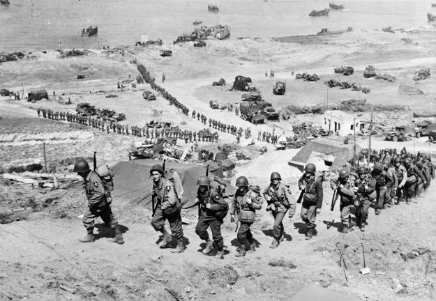U.S. Army reinforcements march up a hill past a German bunker overlooking Omaha Beach after the D-Day landings near Colleville sur Mer, France, June 18, 1944. (REUTERS/US National Archives)
