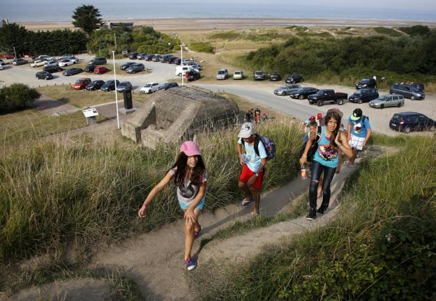 Youths hike up a hill past an old German bunker overlooking the former D-Day landing zone of Omaha Beach near Colleville sur Mer, France, August 23, 2013. (REUTERS/Chris Helgren)
