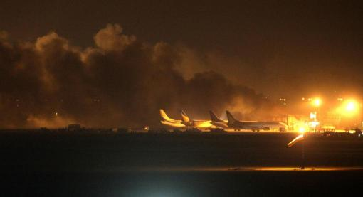 Fire illuminates the sky above Karachi airport terminal where security forces are fighting with attackers Sunday night, June 8, 2014, in Pakistan. (AP Photo/Shakil Adil)