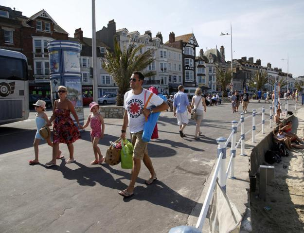 Tourists walk along the beach-front in the Dorset holiday town of Weymouth, England, July 13, 2013. The port was the departure point for thousands of Allied troops who took part in the D-Day landings. (REUTERS/Chris Helgren)