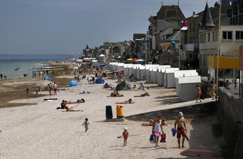 Tourists enjoy the sunshine on the former Juno Beach D-Day landing zone, where Canadian forces came ashore, in Saint-Aubin-sur-Mer, France, August 23, 2013. British and Canadian troops battled reinforced German troops holding the area around Caen for about two months following the D-Day landings in Normandy in 1944. (REUTERS/Chris Helgren)