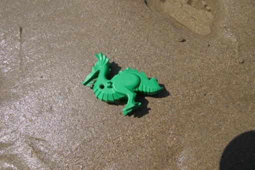 A green Lego dragon on the shore (Tracey Williams/LegoLostAtSea)