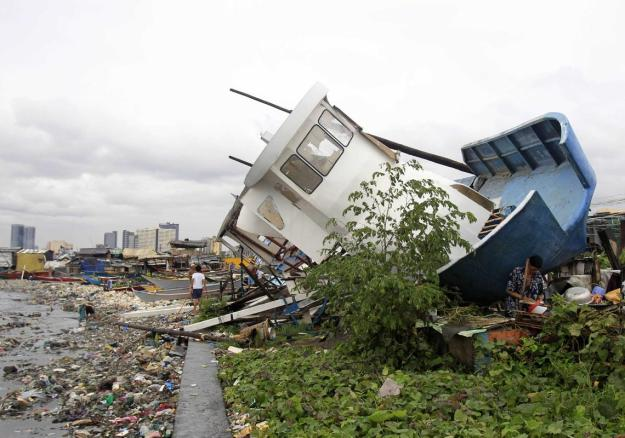 People walk among debris and a boat destroyed by strong winds brought by Typhoon Rammasun in Manila