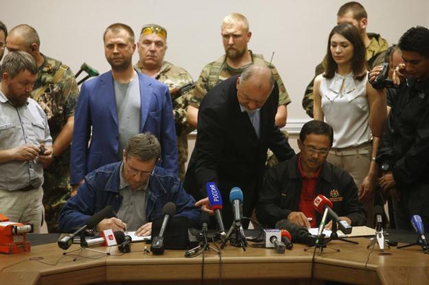A representative (seated L) from pro-Russian separatists and Colonel Mohamed Sakri (seated R) of the Malaysian National Security Council sign documents after the handing over of Malaysia Airlines flight MH17's black boxes, in Donetsk July 22, 2014. The remains of some of the 298 victims of the Malaysia Airlines plane downed over Ukraine were making their way to the Netherlands on Tuesday as Senior Ukrainian separatist leader Aleksander Borodai (back L, in blue blazer) handed over the plane's black boxes to Malaysian experts. REUTERS/Maxim Zmeyev