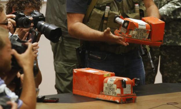 Members of the media take pictures as a pro-Russian separatist places black boxes belonging to Malaysia Airlines flight MH17 on a desk, before their handover to Malaysian representatives, in Donetsk July 22, 2014. The remains of some of the 298 victims of the Malaysia Airlines plane downed over Ukraine were making their way to the Netherlands on Tuesday as senior Ukrainian separatist leader Aleksander Borodai handed over the plane's black boxes to Malaysian experts. REUTERS/Maxim Zmeyev