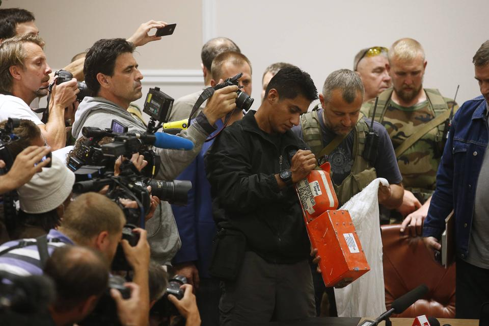 A Malaysian expert (C) examines a black box belonging to Malaysia Airlines flight MH17 during its handover from pro-Russian separatists, in Donetsk July 22, 2014. The remains of some of the 298 victims of the Malaysia Airlines plane downed over Ukraine were making their way to the Netherlands on Tuesday as Senior Ukrainian separatist leader Aleksander Borodai handed over the plane's black boxes to Malaysian experts. REUTERS/Maxim Zmeyev