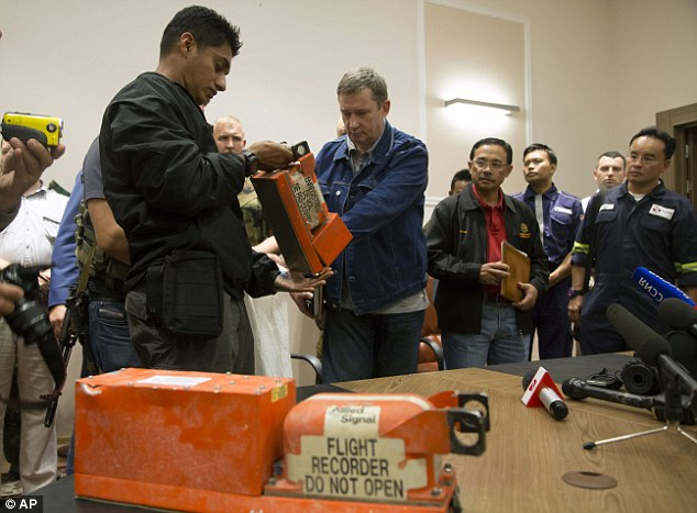 A Malaysian investigator, left, takes a black box from Malaysia Airlines Flight 17 as it is handed over by a Donetsk People's Republic official in the city of Donetsk, eastern Ukraine Tuesday, July 22, 2014. Bowing to international pressure Monday, pro-Moscow separatists released a train packed with bodies and handed over the black boxes from the downed Malaysia Airlines plane, four days after it plunged into rebel-held eastern Ukraine. (AP Photo/Dmitry Lovetsky)