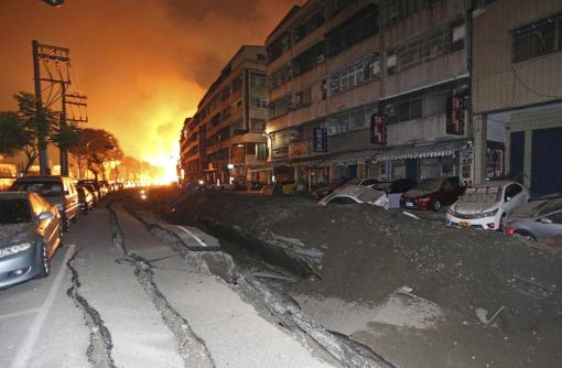 Tossed vehicles line an destroyed street as flames continue to burn from multiple explosions from an underground gas leak in Kaohsiung, Taiwan, early Friday, Aug. 1, 2014. A massive gas leakage early Friday caused five explosions that killed several people and injured over 200 in the southern Taiwan port city of Kaohsiung. (AP Photo)