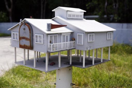 A mailbox in the shape of a house with a veranda and a parking lot is seen along the highway US-1 in the Lower Keys near Key Largo in Florida, July 10, 2014. (REUTERS/Wolfgang Rattay)
