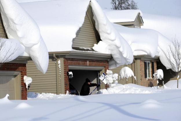 Snowdrifts create a beautiful setting as a man tries to dig out his driveway on Bowen Rd in Lancaster, N.Y. Wednesday, Nov. 19, 2014. A lake-effect snow storm dumped over five feet of snow in areas across Western New York. Another two to three feet of snow is expected in the area, bringing snow totals to over 100 inches, almost a years' worth of snow in three days. (AP photo/Gary Wiepert)