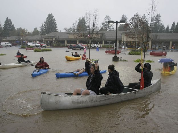 People use kayaks and a canoe to make their way around a flooded parking lot at a shopping center in Healdsburg, Calif.  (Photo: Eric Risberg, AP)