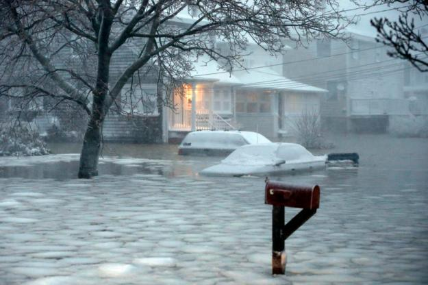 Water floods a street on the coast in Scituate, Mass., Tuesday, Jan. 27, 2015. A storm packing blizzard conditions spun up the East Coast early Tuesday, pounding parts of coastal New Jersey northward through Maine with high winds and heavy snow. (AP Photo/Michael Dwyer)