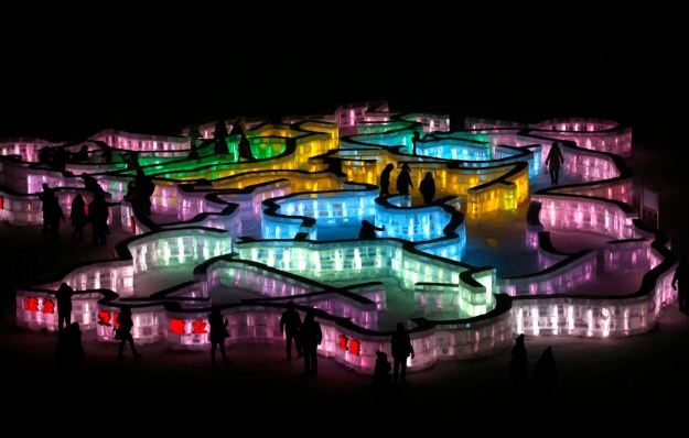 People visit a maze which was built by ice bricks and illuminated by coloured lights during a trial operation ahead of the 31st Harbin International Ice and Snow Festival in the northern city of Harbin, Heilongjiang province, January 4, 2015. (REUTERS/Kim Kyung-Hoon)