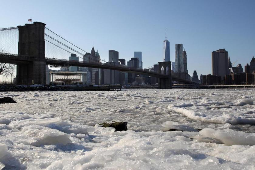 Ice forms on the Brooklyn waterfront in New York on Sunday, Feb. 15, 2015. An extremely cold air mass is moving into the region on Sunday night. The Brooklyn Bridge and One World Trade Center appear in the background. (AP Photo/Peter Morgan)