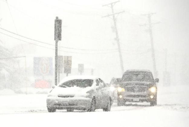 Vehicles move slowly on the road as snow falls Saturday, Nov. 21, 2015, in Wheeling, Ill. The first significant snowstorm of the season blanketed some parts of the Midwest with more than a foot of snow and more was on the way Saturday, creating hazardous travel conditions and flight delays. (AP Photo/Nam Y. Huh)