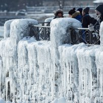 Visitors take pictures near the brink of the ice covered Horseshoe Falls in Niagara Falls, Ontario, Canada, January 3, 2018. REUTERS/Aaron Lynett